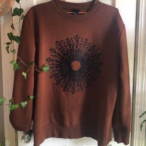 Dark Orange sweater with embroidered design.